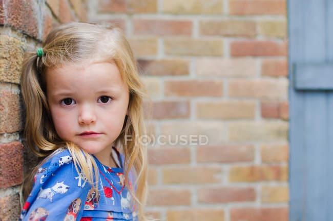 Retrato de menina loira encostada contra a parede de tijolo — Fotografia de Stock