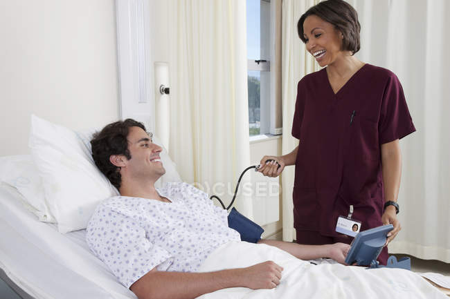 Happy young man in medical clinic office with female doctor — Stock Photo