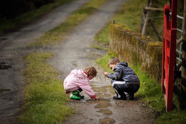 Два маленьких детей, сидя на пути и играя с грязью — стоковое фото