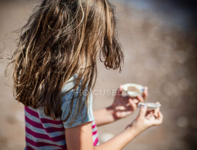 Крупным планом Девушка с морскими раковинами на пляже — стоковое фото