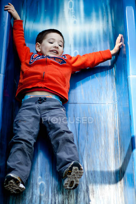 Cute little boy having fun on a slide in playground — Stock Photo