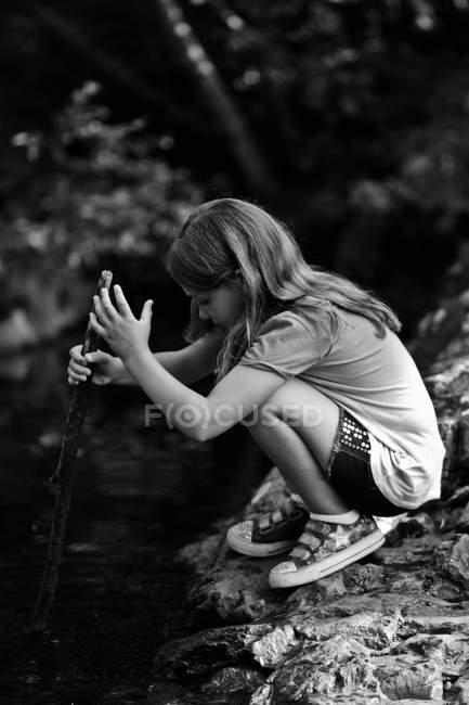 Chica de pie en la roca y palillo en el río - foto de stock