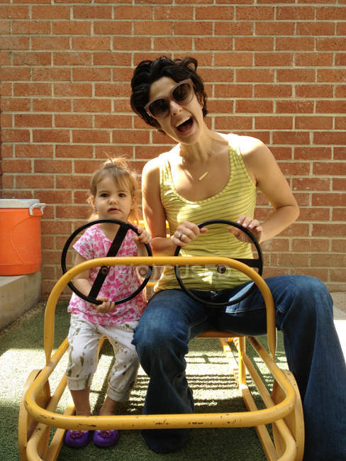 Mother and daughter driving cart — Stock Photo