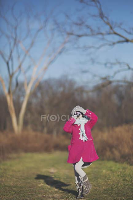 Дівчина дивиться в бінокль в Осінній Парк — стокове фото