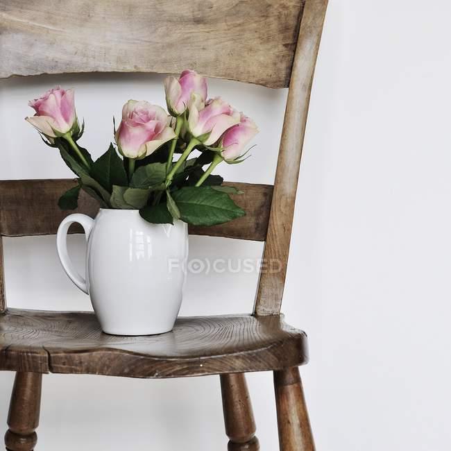 Ваза из красивых розовых роз на деревянном стуле — стоковое фото
