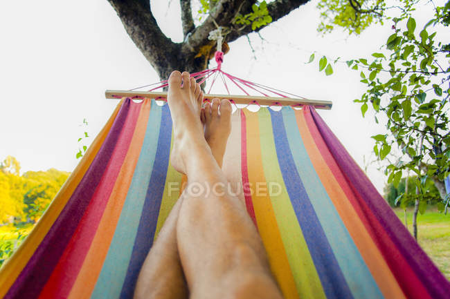 Cropped image of male feet relaxing in colorful hammock — Stock Photo