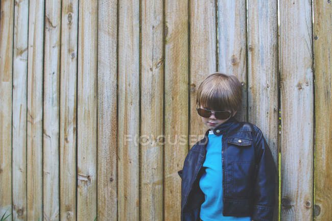 Boy wearing sunglasses posing against fence — Stock Photo