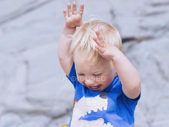 Nahaufnahme Porträt eines entzückenden kleinen Jungen, der mit erhobenen Armen lacht — Stockfoto