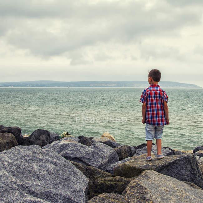 Ragazzo in piedi sulle rocce e guardando il mare — Foto stock