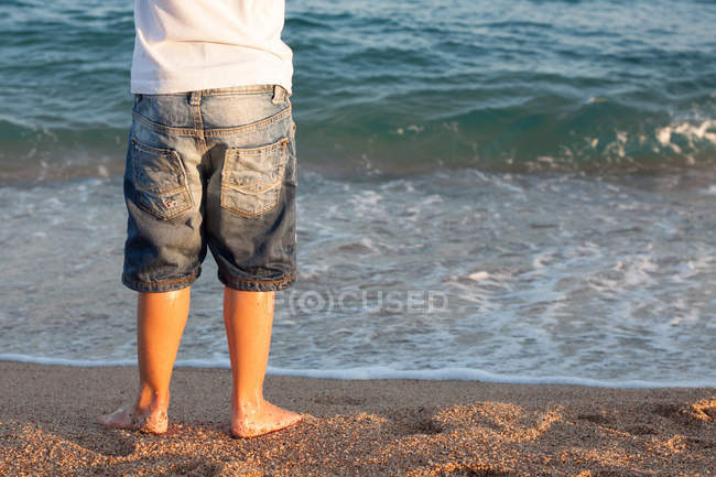 Close-up of male legs standing on beach — Stock Photo