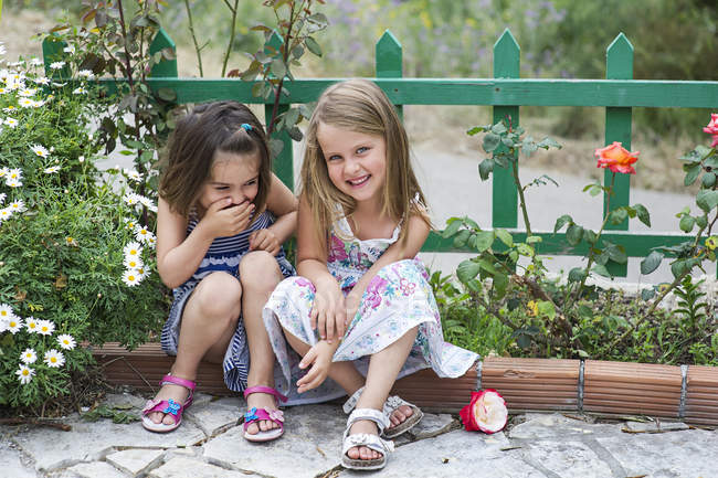 Girls sitting outdoors and laughing — Stock Photo