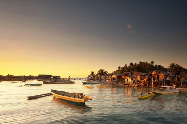 Malaysia, Sabah, Small boats and Sea Gypsy huts at sunrise — Stock Photo