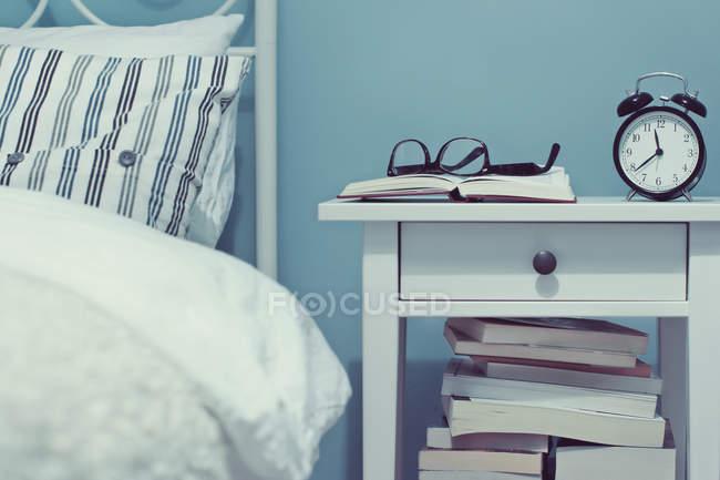 В приміщенні переглянути з нічним столиком з книги та будильник — стокове фото