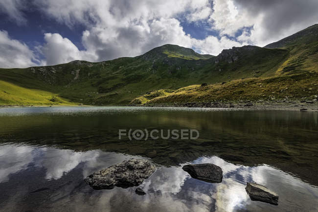 Vista panorámica del majestuoso paisaje con montañas y lago bajo cielo nublado - foto de stock