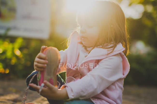 Retrato de niña quitándose el zapato a la luz del sol - foto de stock