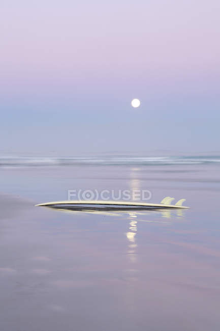 Scenic view of sun over water horizon with surfboard — Stock Photo