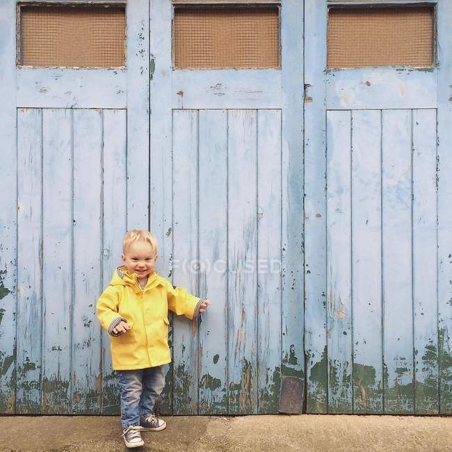 Cute smiling little boy in yellow raincoat standing outside locked doors — Stock Photo