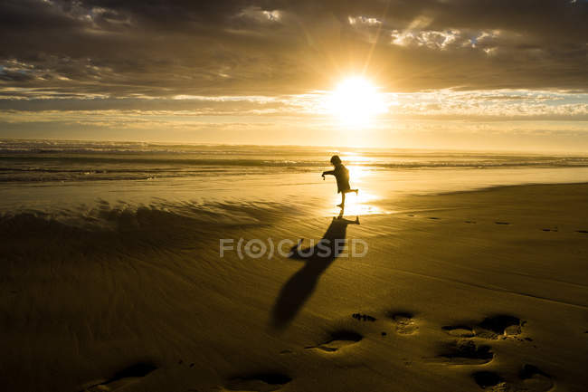 Silhouette of girl dancing on beach at sunset — Stock Photo