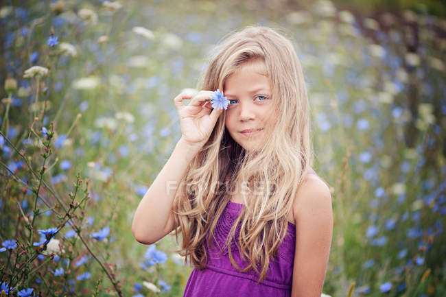 Portrait of blond girl standing in chicory field — Stock Photo