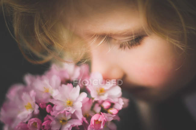 Primer plano de niña rubia que huele a flores - foto de stock