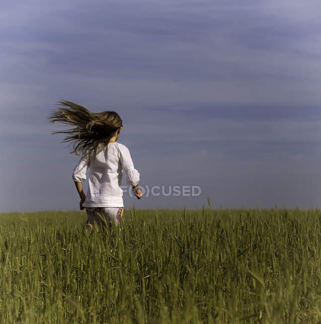 Little girl running in green field — Stock Photo