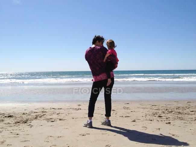 Мать дочь Холдинг на пляже — стоковое фото
