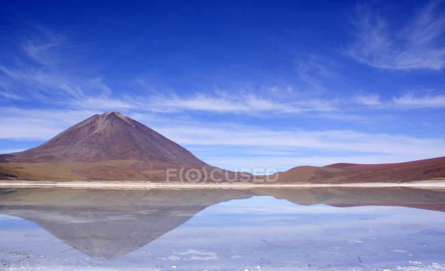 Величним видом знаменитий вулкан Ліканкабур, дзеркальне відображення у воді, Болівія — стокове фото