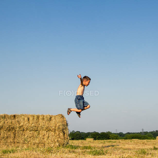 Мальчик прыгает с тюка сена в сельской местности — стоковое фото