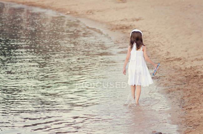 Chica con vestido blanco caminando en el mar - foto de stock
