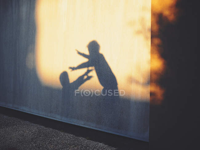 Shadows of two children playing against wall — Stock Photo