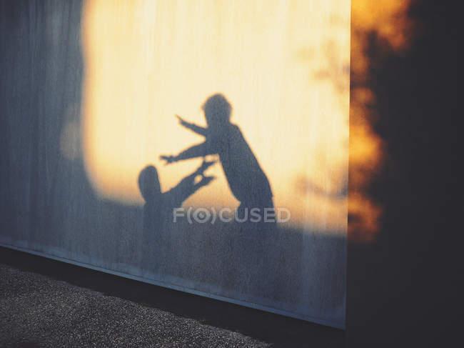 Sombras de dos niños jugando contra la pared - foto de stock