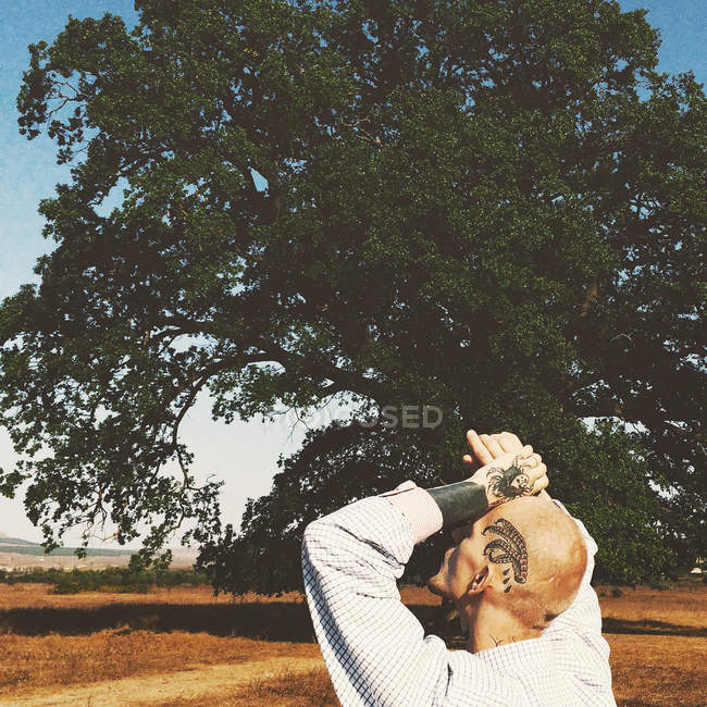 Ritratto di un uomo con i tatuaggi sulle braccia e la testa alzando lo sguardo nella natura — Foto stock