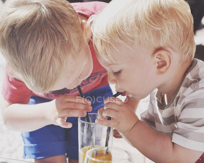Two cute boys drinking juice by straws from one glass — Stock Photo