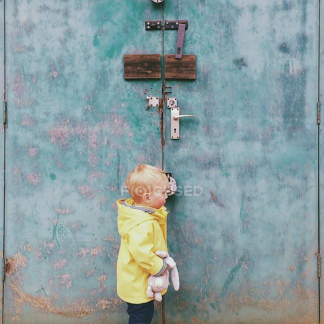 Мальчик, стоящий снаружи запертой потрепанной двери — стоковое фото