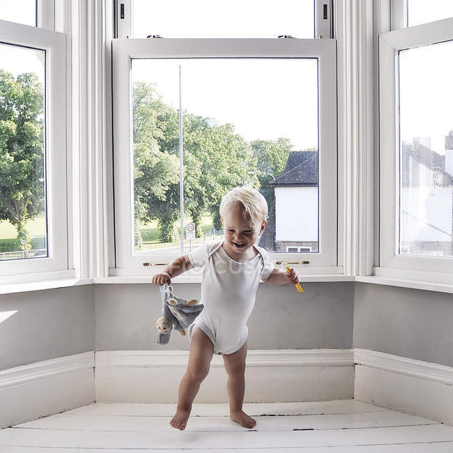 Cute little boy dancing at home with soft toy — Stock Photo