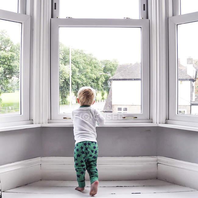 Маленький мальчик, выглядывающий из окна дома — стоковое фото