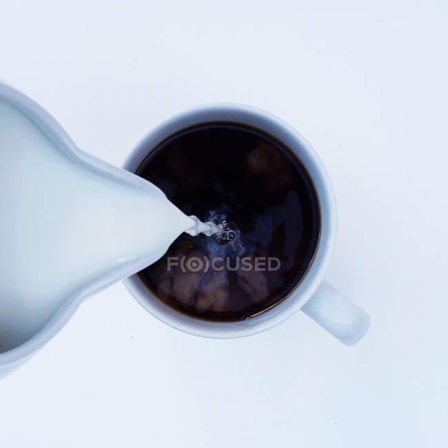 Vista aérea de la leche que se vierte en una taza de café - foto de stock