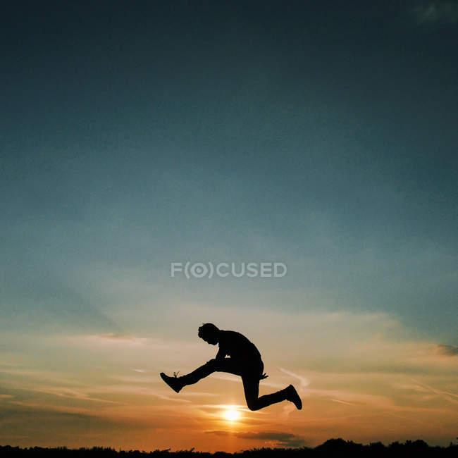 Silueta de hombre saltando sobre sol y cielo despejado - foto de stock