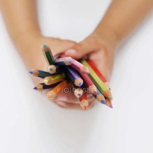 Image recadrée des mains de l'enfant tenant des crayons de couleur — Photo de stock
