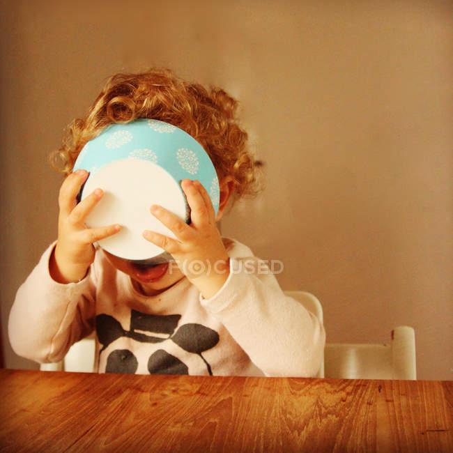 Девушка держит миску с едой перед лицом — стоковое фото