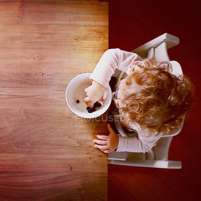 Вид сверху девочка ест чернику деревянным столом — стоковое фото