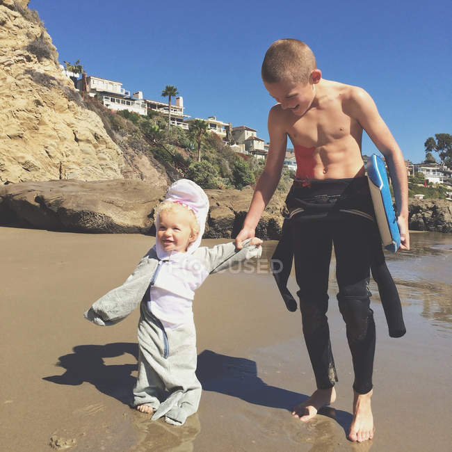 Два брата, взявшись за руки на пляже с доски для серфинга — стоковое фото