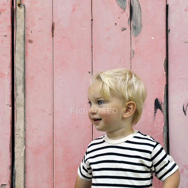 Portrait of a smiling boy standing in front of a pink fence — Stock Photo