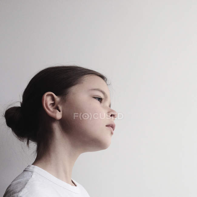 Portrait of pensive girl standing against white background — Stock Photo