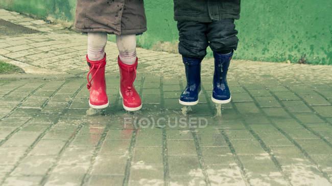 Imagem cortada de duas crianças pulando na poça de água — Fotografia de Stock
