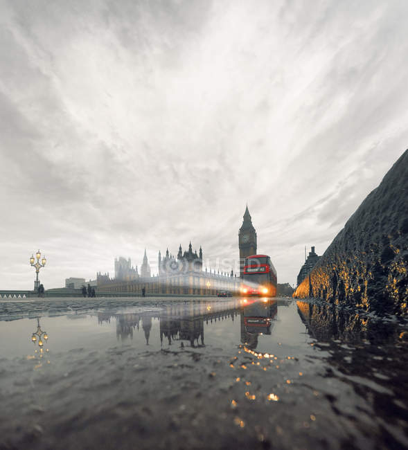Westminster Bridge in rain with incoming double-decker bus, London, UK — Stock Photo
