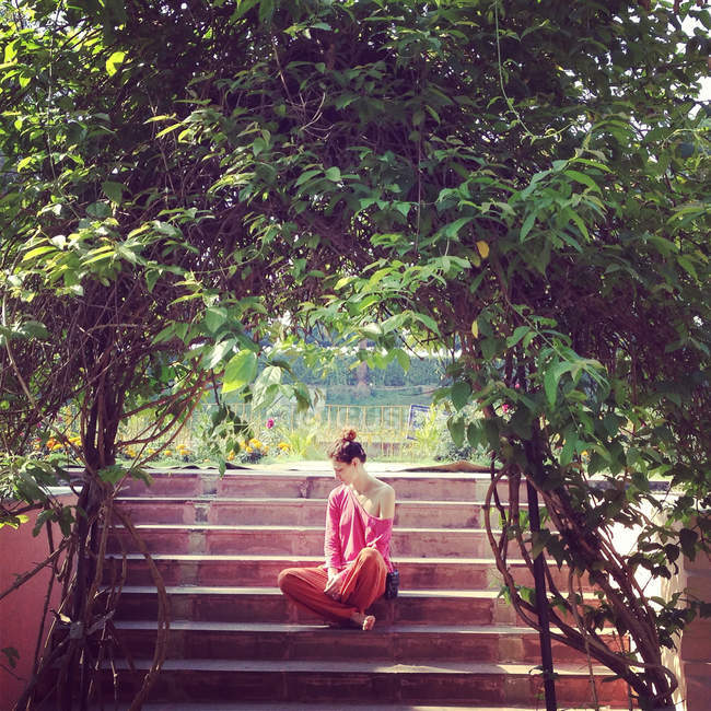 Jovem mulher pensativa sentada em degraus no jardim — Fotografia de Stock
