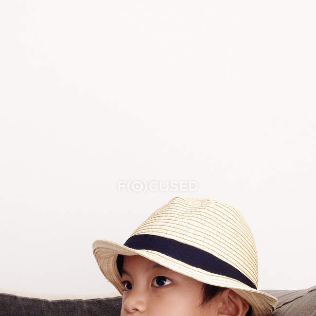 Portrait of serious boy wearing straw hat on white background — Stock Photo
