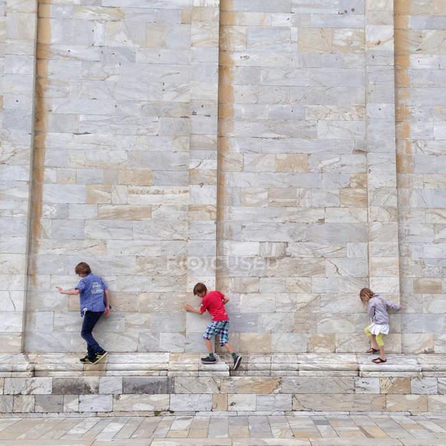 Three little adventurers on wall — Stock Photo
