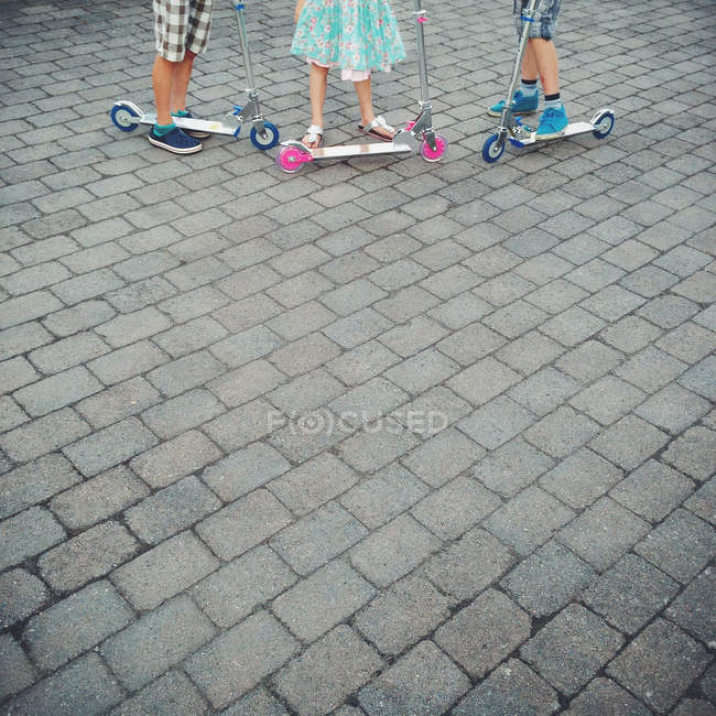 Three children standing next to scooters outdoors — Stock Photo